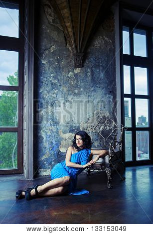brunette woman wearing a blue dress in the room with old walls and furniture
