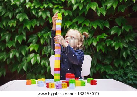 Toddler girl playing with constructor, building a tower in a green garden on wooden table.