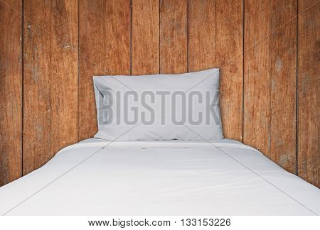 Close up white bedding and pillow on wooden texture background, stock photo
