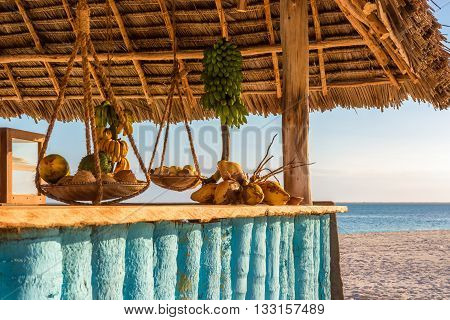 In the picture beach bar in Nungwi ( Zanzibar ) at sunset with exposed coconut banana and tropical fruit .This bar is made with cane bamboowooden and straw rope.
