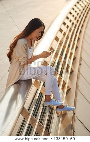 Cheerful young woman sitting outdoors and using smartphone
