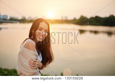 Cheerful attractive young woman standing at rive and