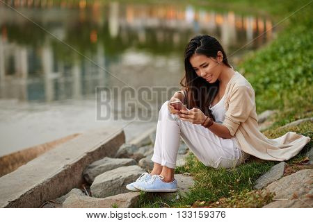 Vietnamese young woman sitting at river and using app in her phone