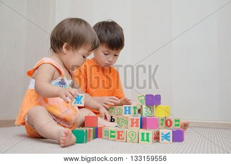 Brother And Little Sister Constructing With Toy Cubes