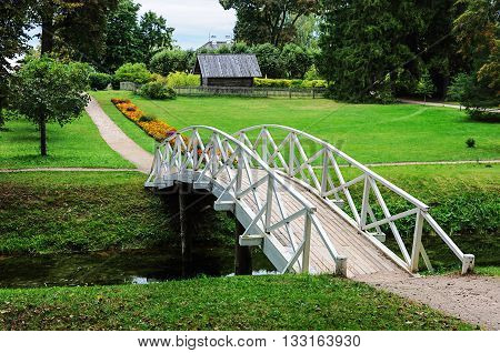 White wooden bridge in old park of the village Mikhailovskoye Pushkinskiye Gory Reserve Russia