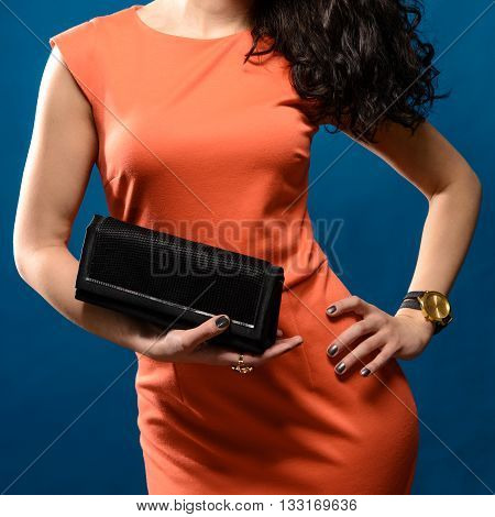 Fashionable woman in red evening dress with a black handbag in her hands on blue background
