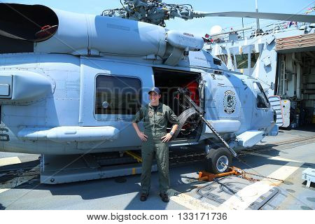NEW YORK - MAY 26, 2016: Navy helicopter pilot in the front of Sikorsky MH-60R Seahawk on the deck of US guided missile destroyer USS Bainbridge during Fleet Week 2016 in New York