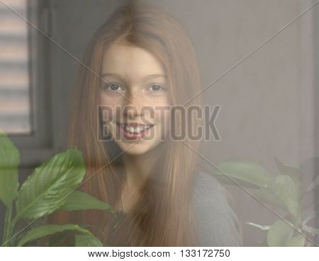 Red-haired girl is smiling and looking out the window