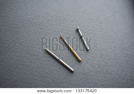 Different dental bur tools close-up. Dental equipment for cleaning cavities in teeth. Several kinds of bur tools for dental manipulations on gray background.