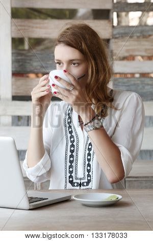 Young woman using laptop while drinking tea