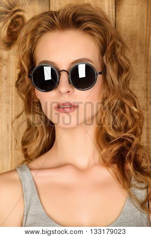 Attractive young woman with foxy hair posing by a wooden wall in casual clothes and sunglasses.