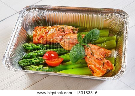Healthy lunch box. Creative healthy food. Healthy vegetarian lunch, Take away organic food. Weight loss diet, food take away in aluminium box. Grilled salmon steak with asparagus and cherry tomato