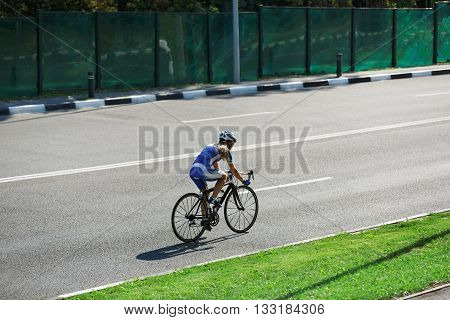 Cycling training on the sunny road. Sport bicycle. Woman cycling on countryside summer road or highway. Training for triathlon or cycling competition. Highway cycling, evening light