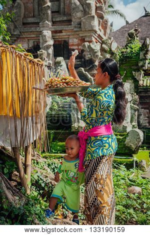 UBUD, INDONESIA - MARCH 01: Balinese woman with little son making offerings in the temple Ubud Bali Indonesia on March 01 2016