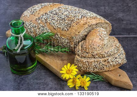 Whole wheat bread and rye sprinkled with sunflower seeds poppy seeds sesame seeds sliced on the board next to a jar of olive oil rosemary and yellow daisies on a dark background