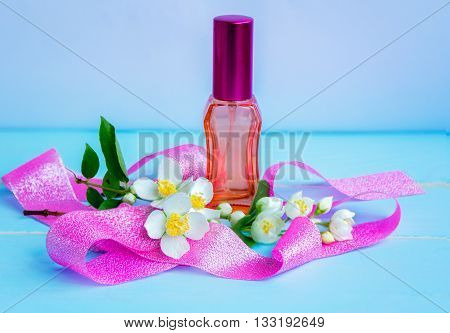 perfume with jasmine essence concept - red glass bottle, glistering pink ribbon and blooming jasmine branch with white flowers