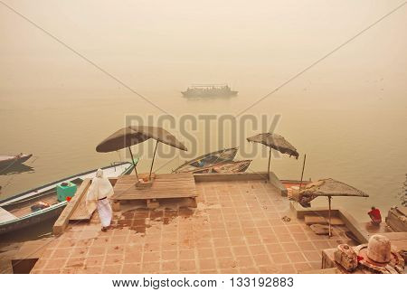 VARANASI, INDIA - JAN 4, 2016: Riverboats in fog of morning scene on Ganges river with old docks and boats on January 4, 2016. Varanasi urban agglomeration had population of 1435113