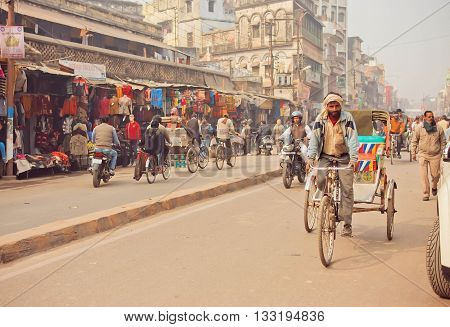 VARANASI, INDIA - JAN 4, 2016: Man driving rickshaw bicycle on busy road with many stores and old buildings of indian city on January 4, 2016. Varanasi urban agglomeration had a population of 1,435,113