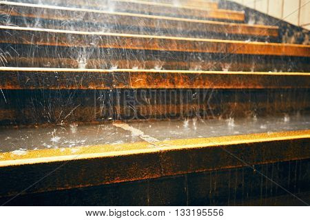 Heavy rain in the city. Rain droplets on the staircase during downpour.