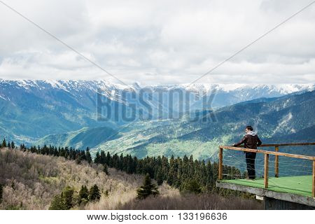 Young man looking at the view from a top a mountain.