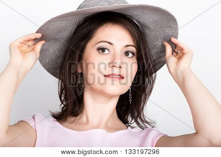 beautiful young brunette woman holding a broad-brimmed hat, she hides her face behind a hat. girl flirting concept. expression of different emotions.