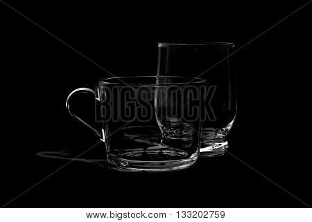 Two empty glass cups on black background in B+W photo