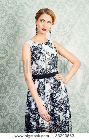Portrait of a beautiful woman in elegant evening dress posing over vintage background. Jewellery. Fashion shot. Hairstyle.