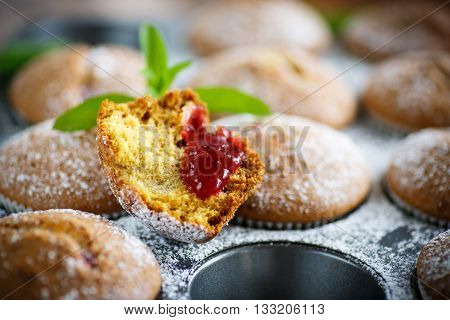 sweet baked muffins with jam inside in powdered sugar