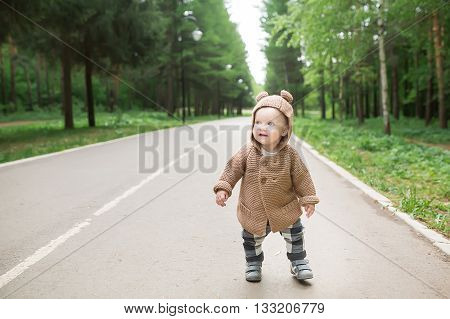 A one year old baby boy taking some of his first steps outdoors in spring park. Cute toddler walking in the green forest in summer