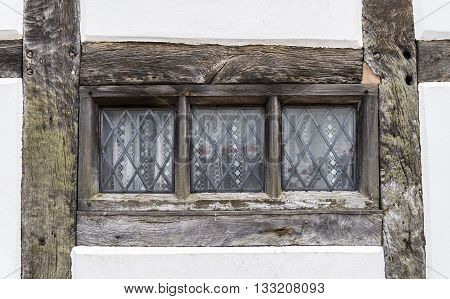 Traditional Tudor style window frame, with wooden beams surrounding the glass pane