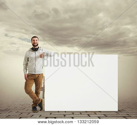 Caucasian bearded man in casual clothes is standing with his elbow resting on a big white poster over virtual reality visualization of cloudy sky and lonely street with paving and bench