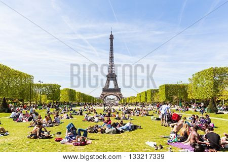 PARIS FRANCE - MAY 5 2016: Lots of people relaxing and having fun on Champ de Mars with the Eiffel Tower on background on a sunny day.