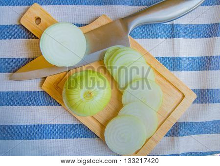 Onions, sliced on wooden cutting Board with a knife, striped napkin.