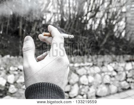 Man smoking cigarette on street black and white