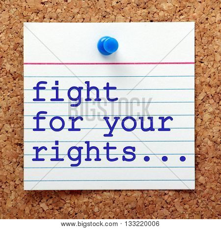 The words Fight For Your Rights in blue text on a note card pinned to a cork notice board asa reminder
