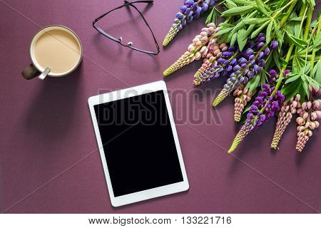 bouquet of flowers on a purple background with a tablet computer with a blank screen.