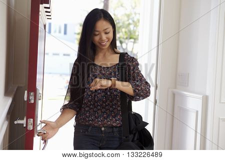 Woman Opening Front Door Whilst Checking Smart Watch