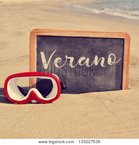 closeup of a chalkboard with a wooden frame and the word verano, summer in spanish written in it, and a diving mask placed on the sand of a beach