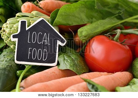 closeup of a house-shaped chalkboard with the text local food placed on a pile of some different raw vegetables, such as cucumbers, tomatoes, carrots or artichokes, on a rustic wooden table