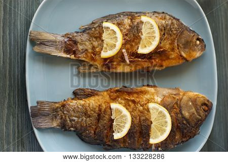 Fried fish on white plate with fork and knife closeup