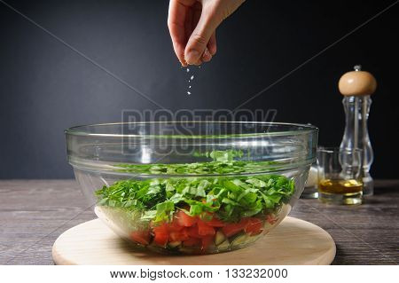 Hand adding salt to vegetable salad. Bowl of fresh green salad, tomatoes, cucumber on wood table against dark background on rustic kitchen. Glass with salt, olive, sunflower oil, pepper on table.