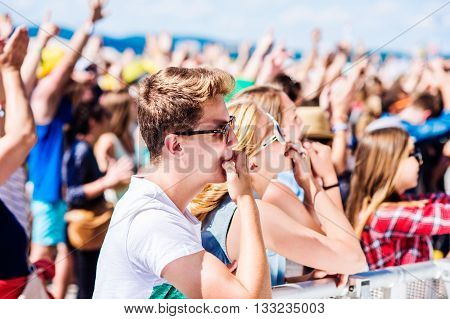 Teenagers at summer music festival under the stage in a crowd enjoying themselves, whistling poster