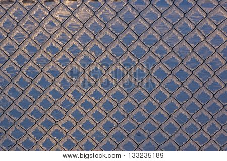 Chain-link fence with snow, winter background, abstract urban design