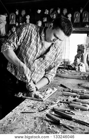 carver in workshop carving with chisel monochrome