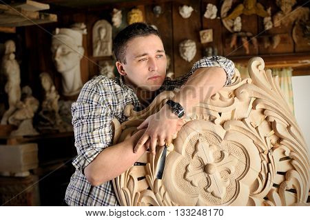 Portrait of young carver in workshop with woodworking