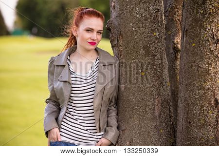 Portrait of beautiful lady posing for photographer outdoors. Redhaired woman with red lips keeping her hands in pockets of jeans.