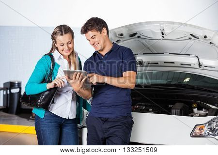 Customer And Mechanic Using Digital Tablet By Car