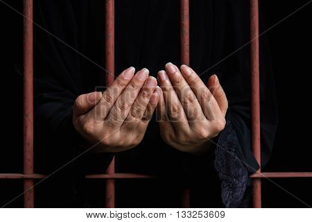 Close up hand of muslim woman praying hang on iron bar in jal.