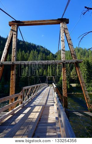 A rustic, wooden foot bridge crosses the Lochsa River in a northern Idaho wilderness area.