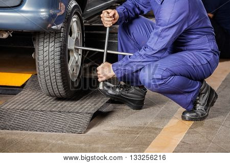 Mechanic Crouching While Fixing Car Tire